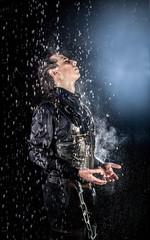 Man in leather under rain imitation in aqua studio