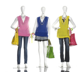 female clothing in jeans with scarf, bag on three mannequin