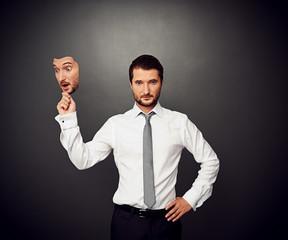 man holding mask with amazed face