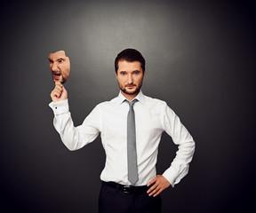 man holding mask with bad mood