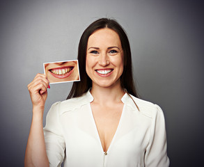 woman holding picture with yellow teeth