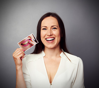 woman holding picture with dirty yellow teeth
