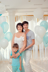 happy family in turquoise costumes against the backdrop of ballo