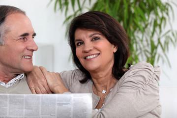 Senior couple reading the newspaper