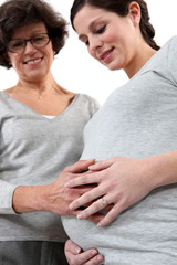 young pregnant woman and mother laying hand on her belly