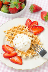 Belgian waffles with strawberries and whipped cream, vertical