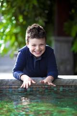 Bambino felice a bordo piscina