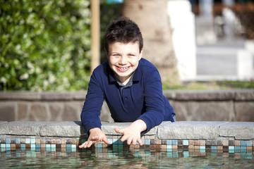 Bambino allegro sul bordo piscina