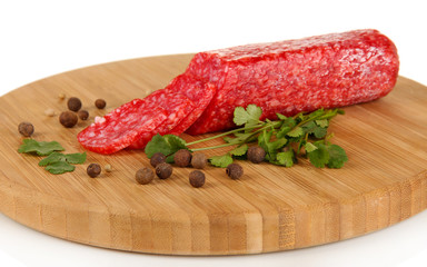 Tasty salami on wooden board isolated on white