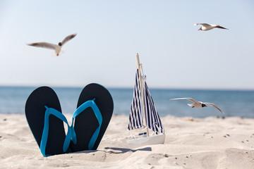 Schuhe und Schiff im Sand umringt von Möwen