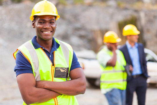 african industrial worker with arms folded