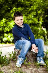 Bambino allegro seduto sul tronco