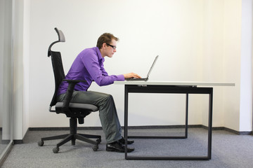 shortsighted businessman bad sitting posture at laptop