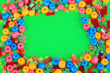 Different colorful beads on green background
