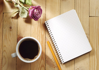 Cup of coffee, dried roses and notebook