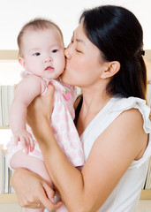 Asian mother kiss her baby girl