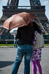 touriste et parapluie devant la tour Eiffel à Paris