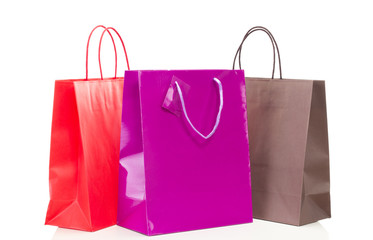 Three colorful shopping bags on white table
