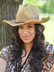 Portrait of beautiful brunette woman with straw hat outdoors