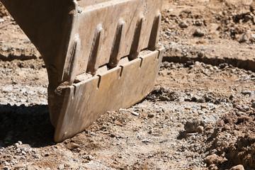 Baggerschaufel steht mit der Grabkralle auf dem Erdboden