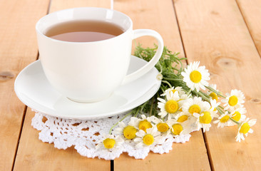 Cup of chamomile tea and chamomile on wooden table