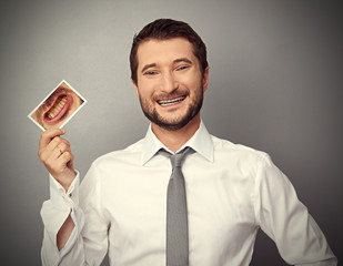 man holding picture with yellow teeth