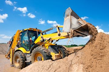 Excavator machine unloading sand during earth moving works