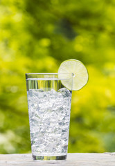 Glass of water and Ice with Lime placed outdoors