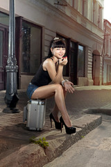 woman sits on suitcase near road