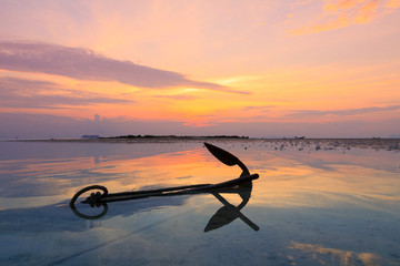 Old anchor in water at sunset