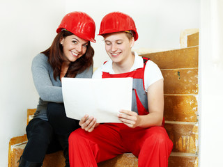 Young worker fixing up a house, discussing in a building lot