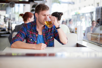 Young man drinking beer in a cafe