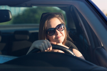 Beautiful businesswoman in sunglasses driving in the car