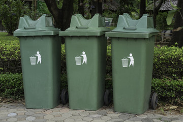 Green plastic recycle bin in park