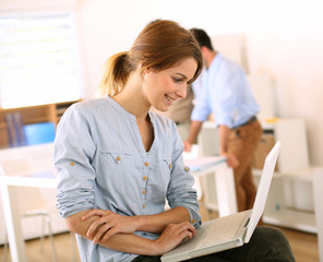 Cheerful girl in office sitting on chair with laptop