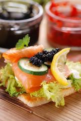 antipasto di crostini con salmone, verdure e uova di lompo