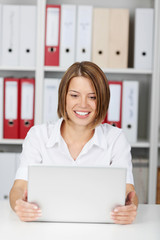 Happy businesswoman looking at laptop computer