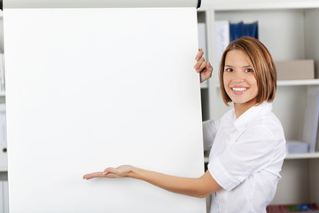 Smiling woman pointing to a flipchart