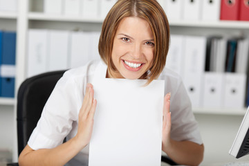 Smiling businesswoman shows white paper