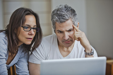 Couple using a laptop at home