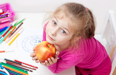 Five years old caucasian blond child girl with apple