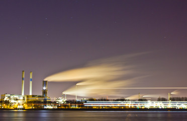 Oil refinery at night with passing boat