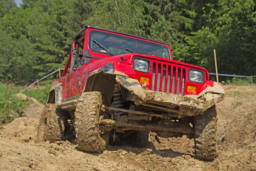 Red off-road vehicle in muddy terrain.