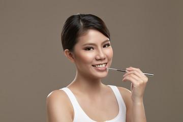 Female asian applying lipgloss
