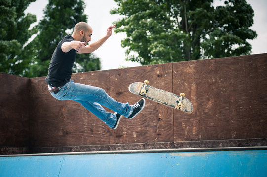 Skateboarder falling from halfpipe at skatepark.