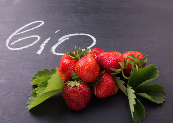 Fresh strawberry on blackboard and word bio on it.