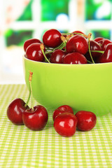 Cherry berries in bowl on table in room