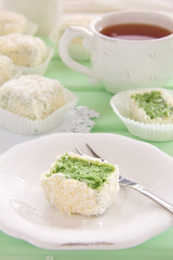 """Cakes """"petit fours"""" with tea and coconut match."""