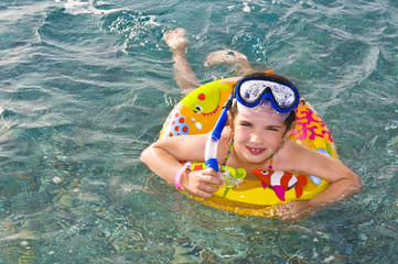 Child in scuba mask swimming on inflatable ring