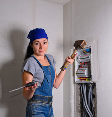 Woman with an electrical box, mallet and hammer